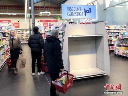 资料图:当地时间3月12日,德国柏林市中心一家大型超市,一名顾客站在被抢购一空的厕纸货架前。随着疫情不断发展,德国也开始出现厕纸和口罩、消毒液等物资被恐慌性抢购的现象。中新社记者 彭大伟 摄