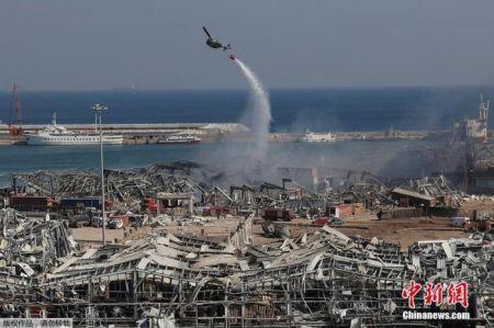图为军用直升机在爆炸现场洒水。
