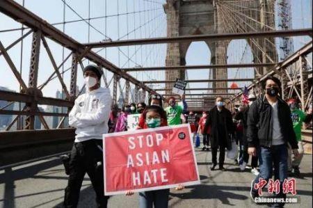 """当地时间4月4日,纽约举行反仇恨亚裔大游行。图为游行队伍中手持""""停止仇恨亚裔""""标语的亚裔孩童。中新社记者 廖攀 摄"""